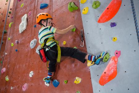 Determined boy practicing rock climbing in fitness studio