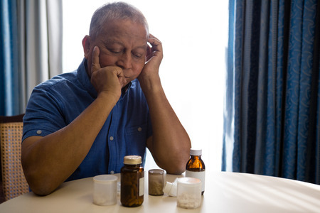 Thoughtful senior man looking at medicines in retirement home