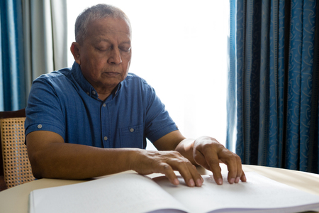 Senior man reading braille book at table in retirement home Stock Photo