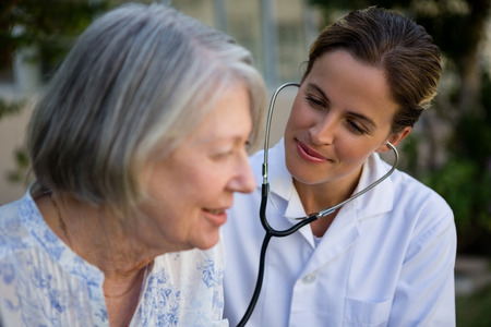 Female doctor examining senior woman with stethoscope in park