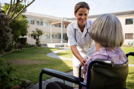 Doctor talking to senior woman sitting on wheelchair at yard Foto de archivo