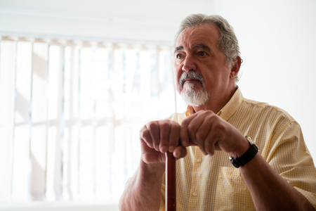 Thougtful senior man looking away while holding walking cane in nursing home