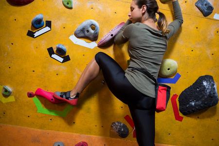 Bepaalde vrouw beoefenen van rotsklimmen in fitnessstudio