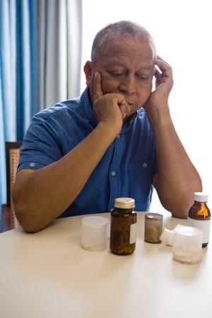 Thoughtful senior man looking at medicines in nursing home