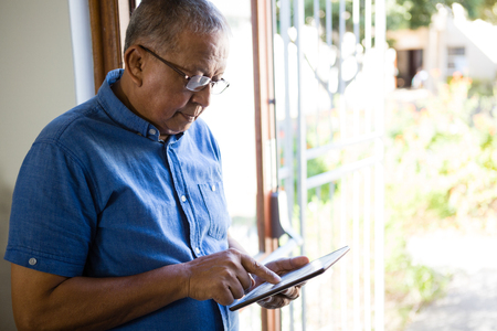 Senior man using digital tablet by window at nursing home