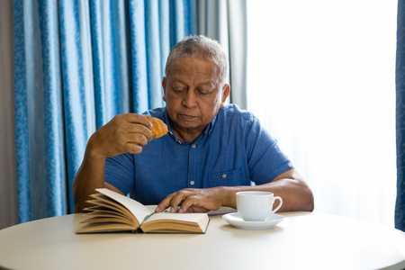 Senior man eating croissant while reading book at table in nursing home Stock Photo