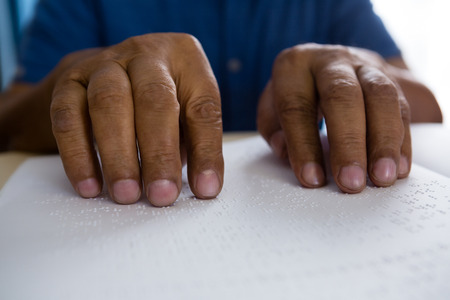 idsection of senior man reading braille book at table in nursing home
