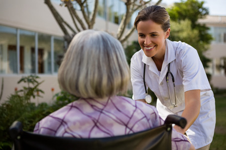 Doctor talking to senior woman sitting on wheelchair at park