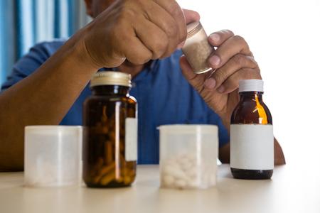 特別養護老人ホームでのテーブルに薬を服用して年配の男性の中央部 写真素材