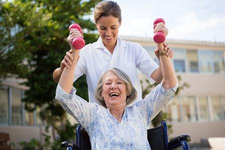 Doctora ayudando a la mujer a levantar pesas en el parque Foto de archivo - 83562249