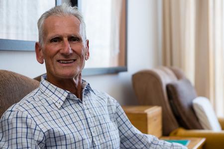 Portrait of smiling senior man relaxing on armchair in nursing home