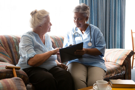 Senior woman discussing with doctor while reading book sofa in nursing home Stock Photo