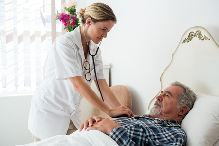 Female doctor listening to heartbeats of senior man lying on bed in nursing home