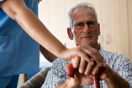 Midsection of female doctor standing by senior man sititng on sofa in retirement home