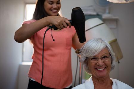 Beautician drying senior woman hair in salon