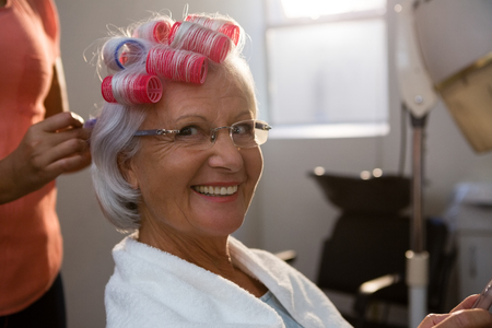 年配の女性の髪を笑顔からカーラーの取り外しのヘアスタイリストの手をトリミング 写真素材
