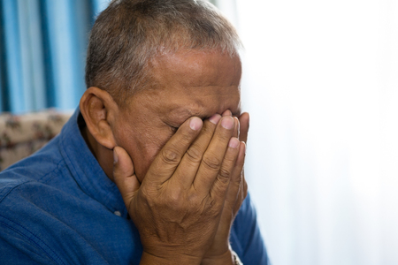 Close up of upset senior man covering eyes with hands in nursing home