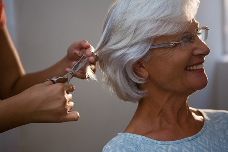 Cropped hands of hairsylist cutting hair of senior woman in salon