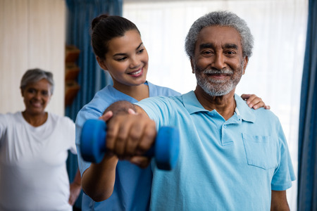Nurse guiding senior man in exercising at retirement home