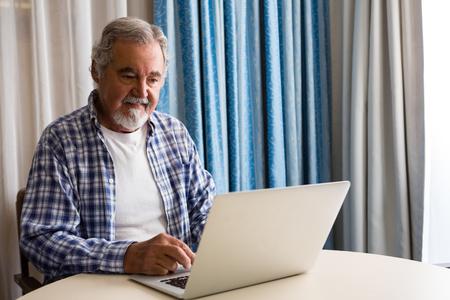 70s: Senior man using laptop while sitting at table in nursing home