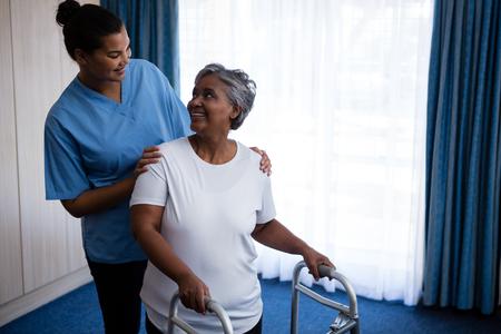 Smiling nurse assisting senior woman in walking with walker at nursing home