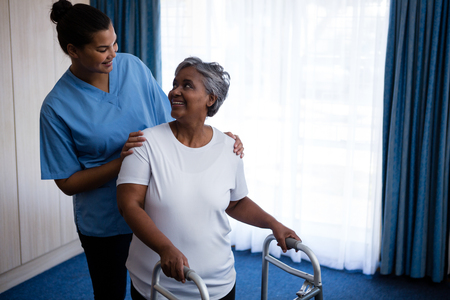Smiling nurse assisting senior woman in walking with walker at nursing home