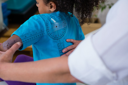 Physiotherapist examining girl patients back with goniometer in the clinic Stock Photo