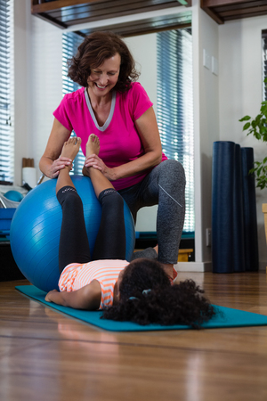 Female physiotherapist helping girl patient in performing stretching  exercise on exercise mat in clinic