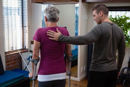Physiotherapist assisting senior woman patient to walk with crutches in clinic