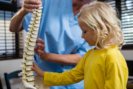 Physiotherapist explaining the spine to girl patient in the clinic