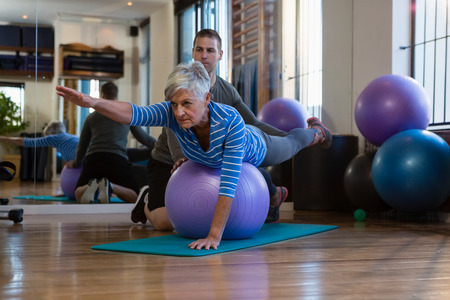 Physiotherapist assisting senior woman in performing exercise on fitness ball at clinic