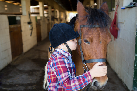 Girl kissing the horse in the stable
