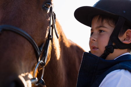 Close-up of rider boy caressing a horse in the ranch
