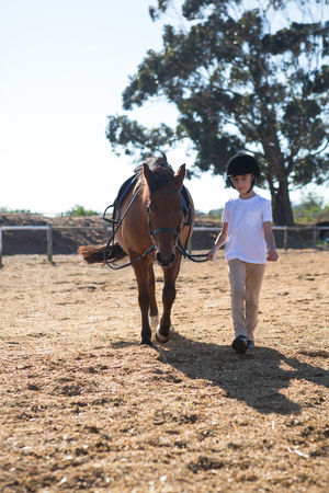 Rider girl walking with a horse in the ranch on a sunny day Stock Photo