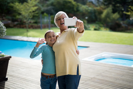 Smiling granddaughter and grandmother taking a selfie near the pool