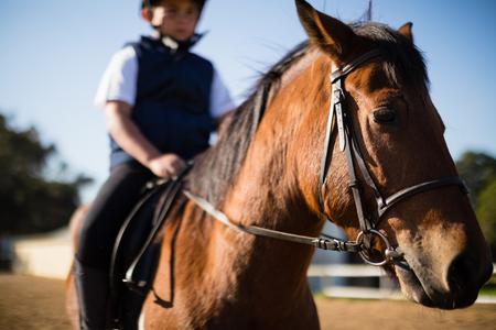 Jongen rijdt een paard in de ranch op een zonnige dag