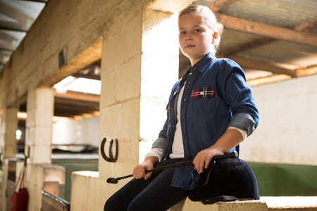 Portrait of girl sitting in the stable