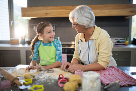 Grandmother and granddaughter cutting dough with a cookie cutter in the kitchen Stock Photo