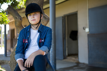 Thoughtful girl sitting on tree trunk near stable