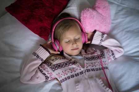 Girl listening to music on headphones while lying on bed in bedroom