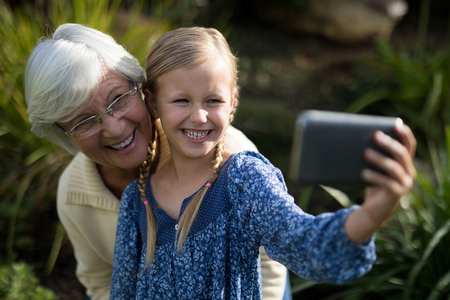 Grandmother and granddaughter taking selfie with mobile phone in garden on a sunny day Stock Photo