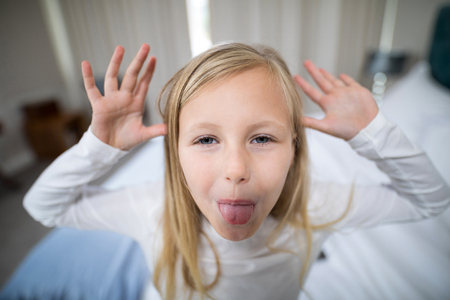 Portrait of girl making facial expression in bedroom at home Banco de Imagens - 83605091