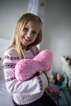 Portrait of smiling girl holding heart shape pillow on bed in bedroom