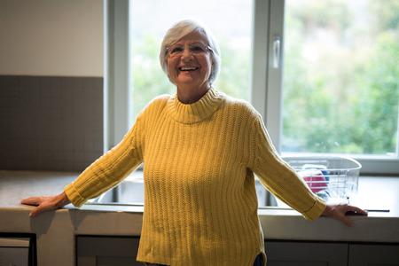 hygienic: Portrait of smiling senior woman standing near kitchen worktop Stock Photo