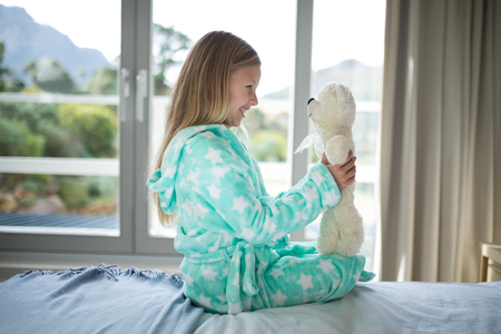 Smiling girl holding teddy bear on bed in bedroom at home
