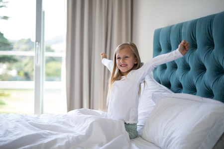 Girl stretching her arms while waking up in bedroom at home