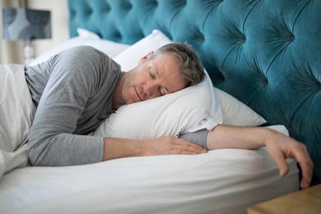Man sleeping on bed in bedroom at home 版權商用圖片