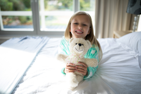 Portrait of smiling girl holding teddy bear on bed in bedroom