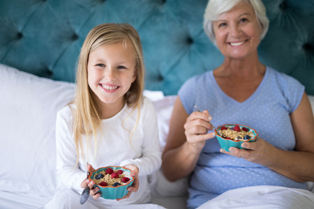 Portrait of smiling granddaughter and grandmother having breakfast on bed