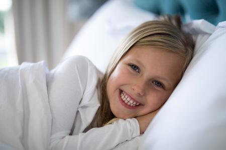 slumber: Portrait of smiling girl lying on bed in bedroom Stock Photo